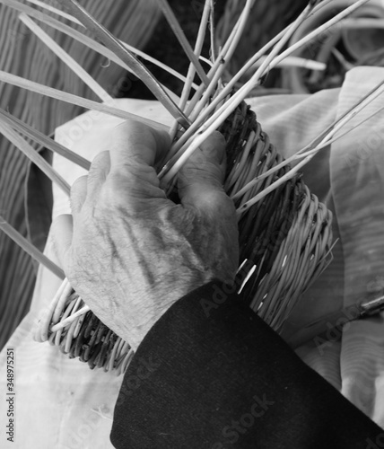 Photo skilled senior craftsman while creating a wicker basket