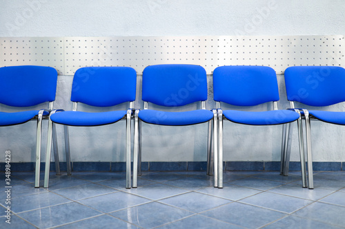 Fotomural Line of empty blue visitor chairs standing near wall at reception or in bank