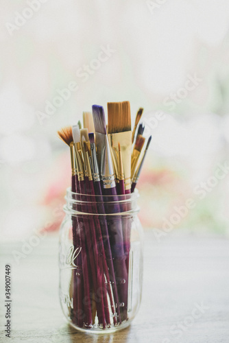 Paint brushes in a glass jar in natural light