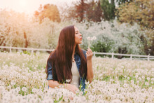 Calm Beautiful Hippie Girl In Denim Jacket Relaxing Sitting On Dandelion Field. Happy Young Carefree Hipster Woman Blowing Dandelion Flowers In Hand On Green Grass. Countryside Nature, Spring Allergy