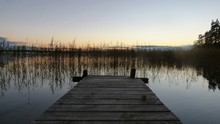 Wooden Pier Over Lake Against Clear Sky At Sunset