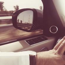 Man Adjusting Side-view Mirror Of Car