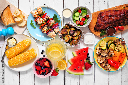 Fototapeta Summer BBQ or picnic food concept. Assortment of grilled meats, vegetables, fruits, salad and potatoes. Top down view table scene with a white wood background. obraz