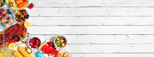 Fototapeta Summer BBQ or picnic food corner border. Assortment of grilled meat, vegetables, fruits, salad and potatoes. Overhead view over a white wood background. Copy space. obraz
