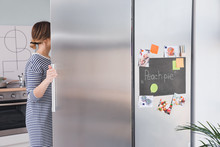 Young Woman Opening Refrigerator In Kitchen