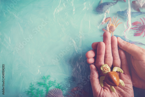 Hands holding turtle on marine sea animals covered with plastic, CSR responsibil Wallpaper Mural
