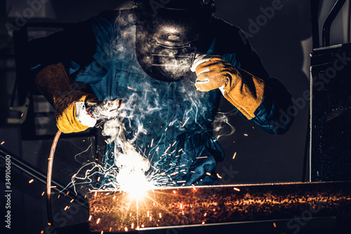 Metal welder working with arc welding machine to weld steel at factory while wearing safety equipment Canvas Print