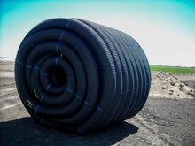 Spool Of HDPE Drainage Tile Sitting In Agricultural Field