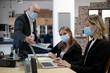 Vorgesetzter und Mitarbeiterinnen mit Gesichtsmasken in einer Besprechung