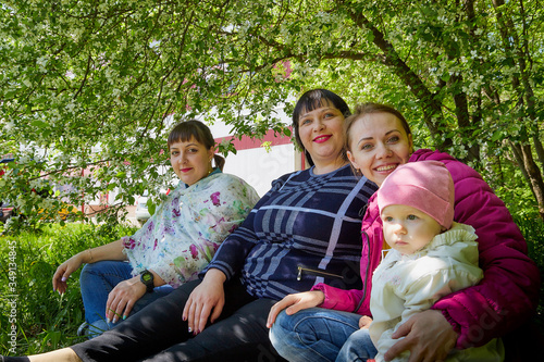 Photo Three different funny women and one small seriously girl in the park full of apple blossom trees in a spring day