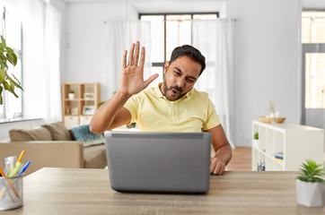 technology, remote job and communication concept - happy indian man with laptop computer having video chat and making high five gesture at home office