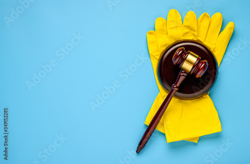 Photo .Rubber gloves and mallet on a blue background. Concept of litigation at a clean