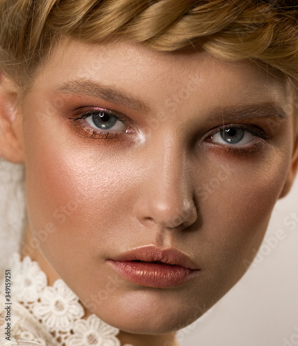 Close-up face of a woman with stylish makeup. Shades of bronze in the eyes. Beige lipstick with a golden lip gloss. Shining healthy skin. Highlighter. Fashion make-up.