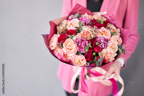 Fototapeta Bright berry color, Beautiful bouquet of mixed flowers in womans hands. the work of the florist at a flower shop. Delivery fresh cut flower. European floral shop. obraz