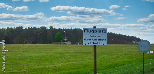 Photo Empty airfield for gliders on a grassy area with a sign with German inscription: