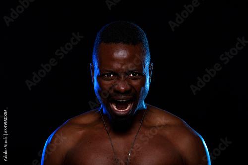 Valokuva Hombre negro sobre fondo negro con gesto furioso