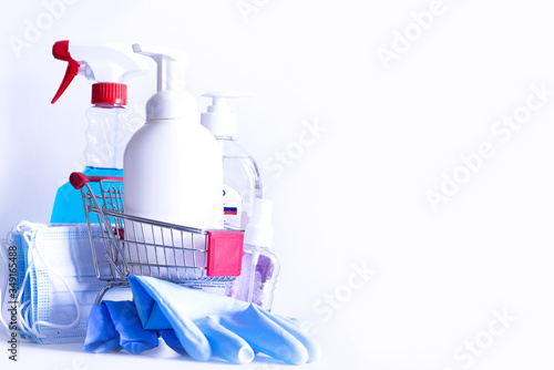 Fototapeta Shopping basket full with disinfection or disinfection cleaning products on white background obraz