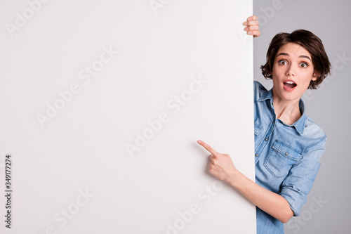 Fototapeta Photo of funny pretty cheerful lady holding hands paper direct finger side white empty space poster proposing buy advert place wear casual denim shirt isolated grey color background obraz