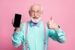 Portrait of amazed excited old man hold new smartphone show thumb up sign recommend suggest select wear teal turquoise shirt purple bowtie isolated over pink pastel color background