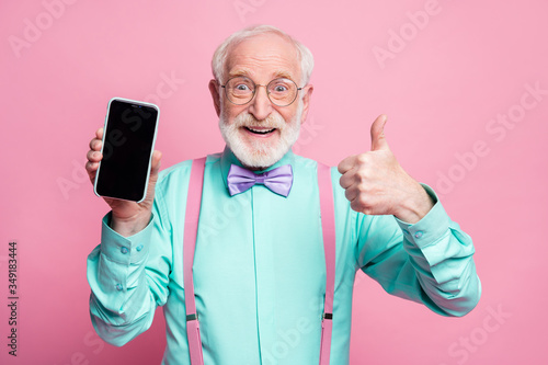 Obraz Portrait of amazed excited old man hold new smartphone show thumb up sign recommend suggest select wear teal turquoise shirt purple bowtie isolated over pink pastel color background - fototapety do salonu