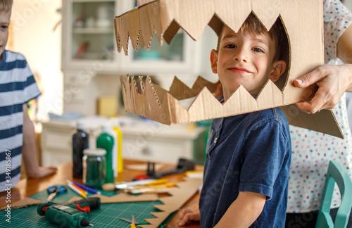 Cuadros en Lienzo Smiling boy wearing a cardboard dinosaur costume