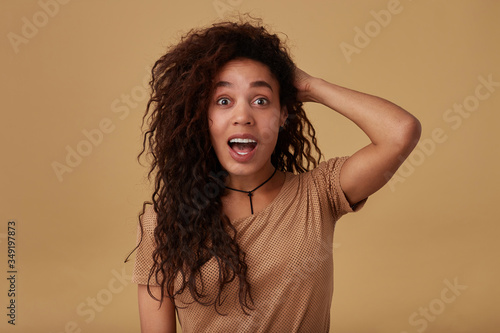 Bemused young lovely curly dark skinned brunette lady holding raised hand on her Canvas Print