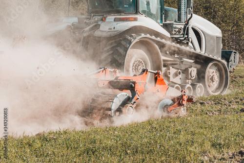 Fotografia, Obraz Agricultural equipment shreds the plowed land