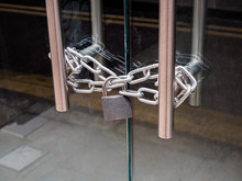 A Retail Shop Glass Front Doors, Padlocked And Chained Shut. For Security And Safety.