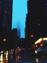 Illuminated City By Fog Covered Chrysler Building Against Clear Sky At Dusk