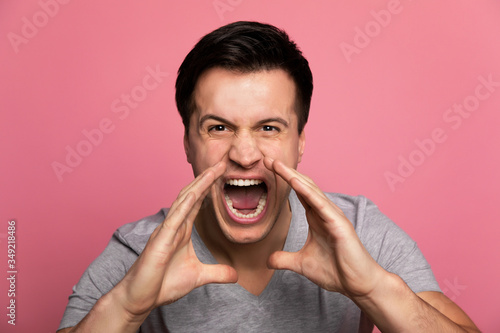 Hear me roar! Close-up shot of a young man in casual clothes, who is screaming while holding his arms near his mouth Canvas Print