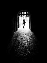 Man Standing At Doorway In Dark Room