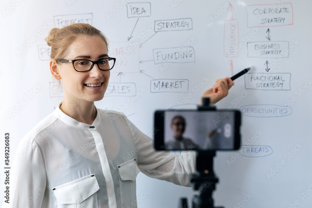 Fototapeta online education, webinar and business vlog concept - woman teaching and recording video with phone in front of whiteboard