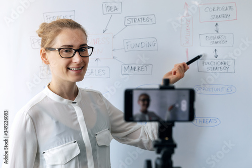 online education  webinar and business vlog concept - woman teaching and recording video with phone in front of whiteboard