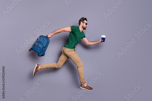 plakat Full body profile side photo of serious guy jump run dont want miss check in passing board hold visa tickets bag backpack wear green trousers isolated over gray color background