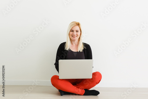 young woman sitting on floor and typing Canvas Print