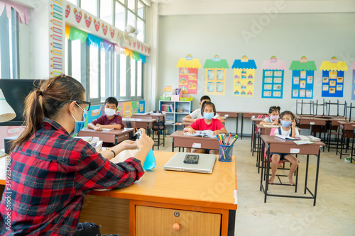 Fotomural Teacher wearing protective mask to Protect Against Covid-19,Group of school kids with teacher sitting in classroom online and raising hands,Elementary school,Learning and people concept