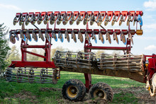 A Red Modern Harrow Stands In A Field Before Sowing. Hydraulic Mechanism For Grinding The Soil After Plowing.