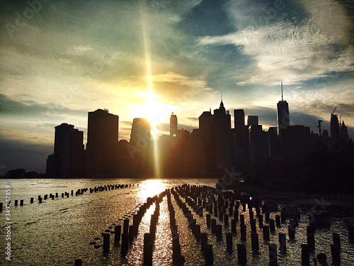 Wooden Posts In Hudson River Against Sky During Sunset In City Fototapeta
