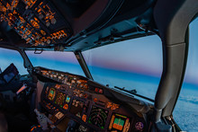 Airplane Cockpit Atmosphere Flying Towards The Oncoming Night At Dusk. Pilot Perspective On Beautiful Sunset From Inside The Flight Deck