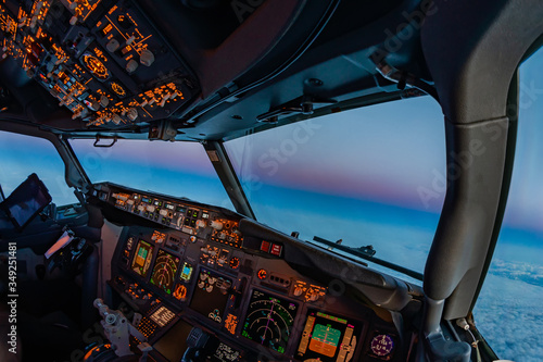 Fotografie, Obraz Airplane cockpit atmosphere flying towards the oncoming night at dusk