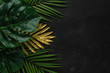 canvas print picture - Creative layout with gold and green tropical palm leaves on black background. Minimal summer abstract pattern.