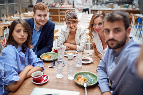 Leinwand Poster group of young caucasian people taking selfie at lunch in restaurant