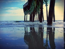 Pier Reflected On Wet Sandy Beach
