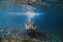 Snorkeler, Snorkeling Man In Full Face Mask, Summer Vacation Activity, Swimming In The Warm Tropical Sea, Seashore And Fishes, Starfishes Near Rocks, Italy. On Distance