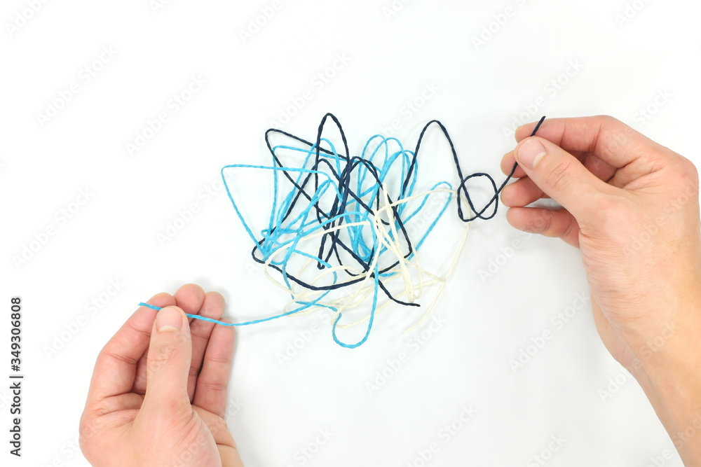 Fototapeta Hand fixing tangled yarn. Critical thinking, problem solving and psychotherapy concept.