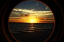 Scenic View Of Beach At Sunset Through Window