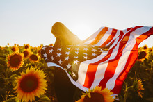 4th Of July. Nice Girl With The American Flag In A Sunflower Field.Freedom. Sunset Light. Independence Day. Patriotic Concept.