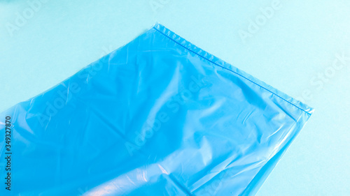 Photo One torn plastic garbage bag in blue on a blue background