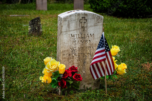 Fototapeta TENNESSE, USA - MAY 25 2019: A headstone or gravestone in Cades Coves with flowers & small flag, marking the grave of an American Revolution Soldier, Memorial day in America for honoring the military