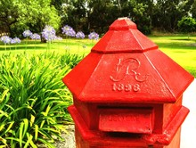 Old Red Public Mailbox Against Trees